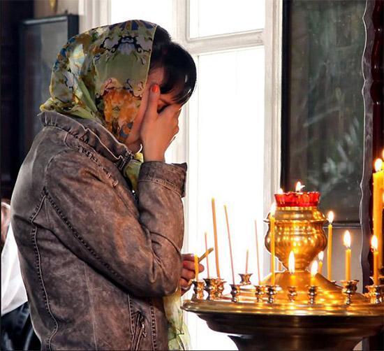 Женщина в храме перед иконой
