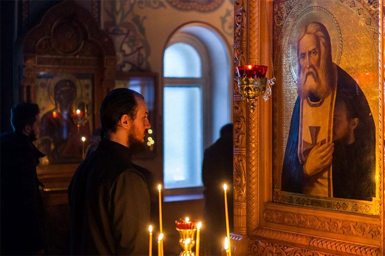 Мужчина перед образом Серафима Саровского в храме