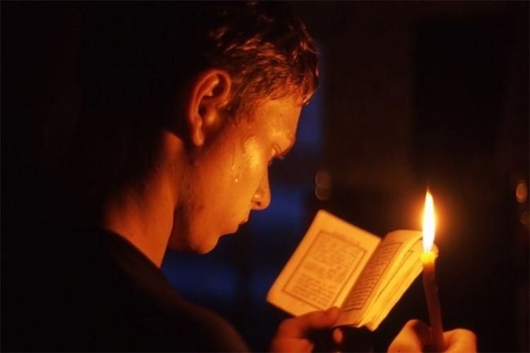 Мужчина со свечой молится