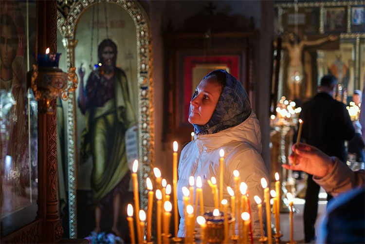 Женщина перед иконой в храме