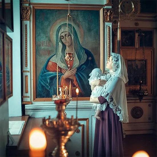 Женщина с младенцем перед иконой Богородицы